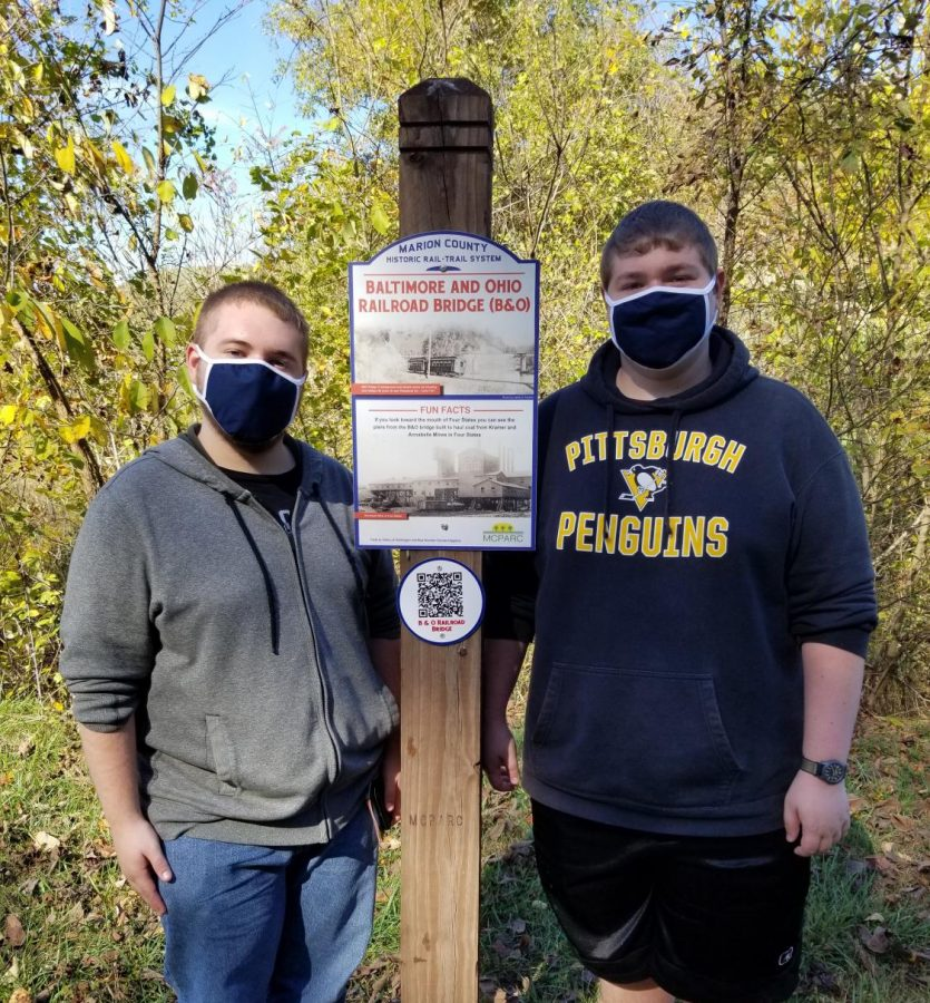 The Taylor brothers, on the left, Mason, and on the right, Chase, stand in front of a sign near the Marion County Historic Rail-Trail System.